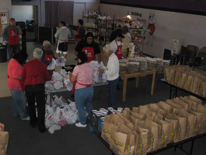Volunteers filling bags of non-perishable food to be given out that day.