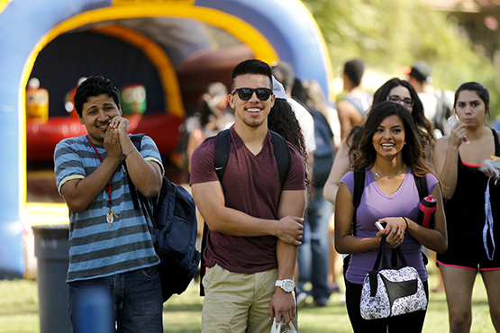 Three students smiling while at the 2014 Homecoming Roundup