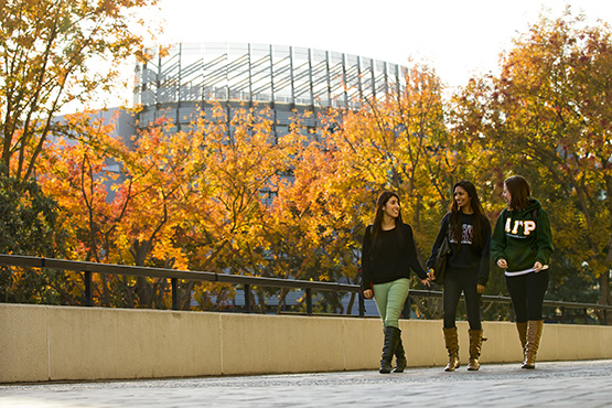 three girls walking on the USU balcony during Fall